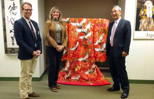 Consul General of Japan Hon. Toshiyuki Iwado, Fulbright Association Chicago Chapter President Mary Mares-Awe, and Vice President Dr. Ron Harvey stand next to a display of a traditional Japanese kimono